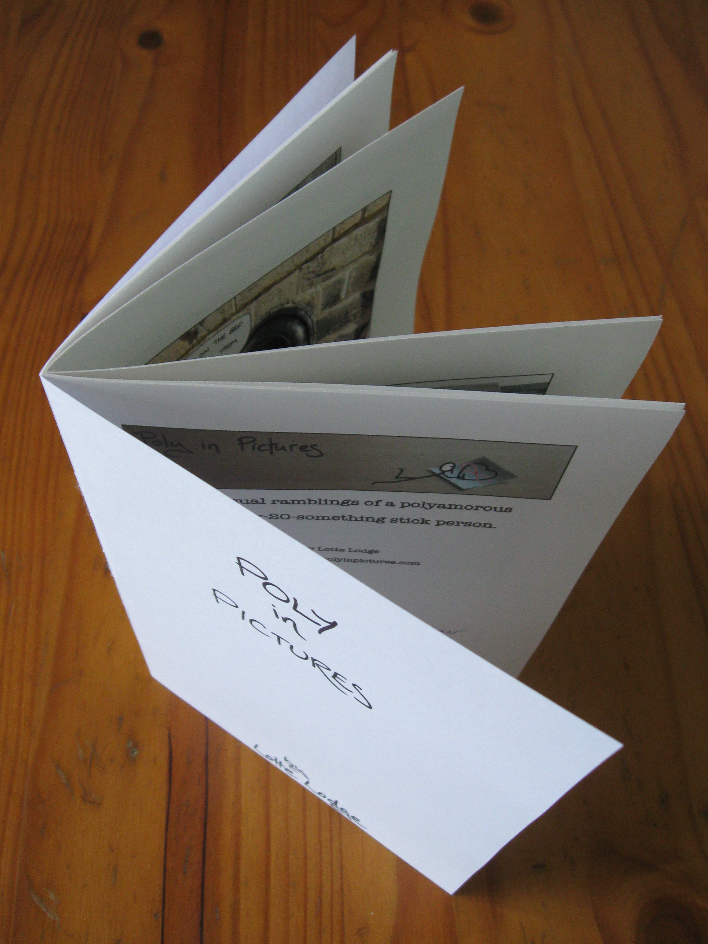 A custom comic booklet I made, photographed from above, as it is standing up like a birthday card on display. The front cover and parts of some of the comics within are visible.