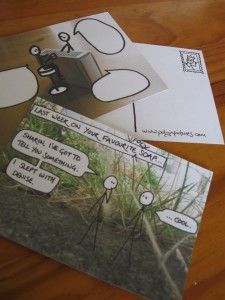 Three postcards. One shows the reverse, with a little mock stamp drawing on it. One shows a PiP comic with the text erased from the speech bubbles. One shows a recent comic in full.