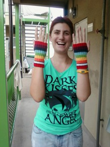 A person wearing a pair of rainbow knitted handwarmers, and looking quite chuffed about it, too.
