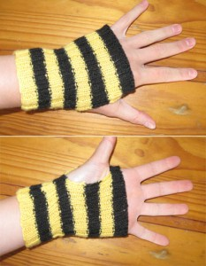 A pair of black and yellow striped handwarmers viewed from the palm and back of the hand. Each glove has alternating yellow and black stripes, four of each colour, and each stretches from knuckles to wrist bone.