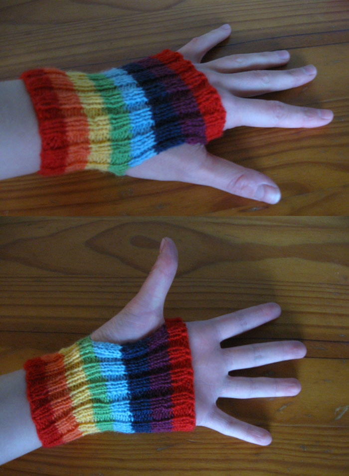 Small rainbow striped ribbed handwarmers, ie: a tube with a thumb hole. They reach from just below the wrist-bone to just on the first finger knuckles. The stripes are bright, as follows, from cuff to knuckle: red, orange, yellow, green, blue, indigo, violet, red.