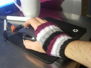 A hand resting on a computer mouse. The hand is wearing a handwarmer knit in the asexual flag colours of black, grey, white and purple.